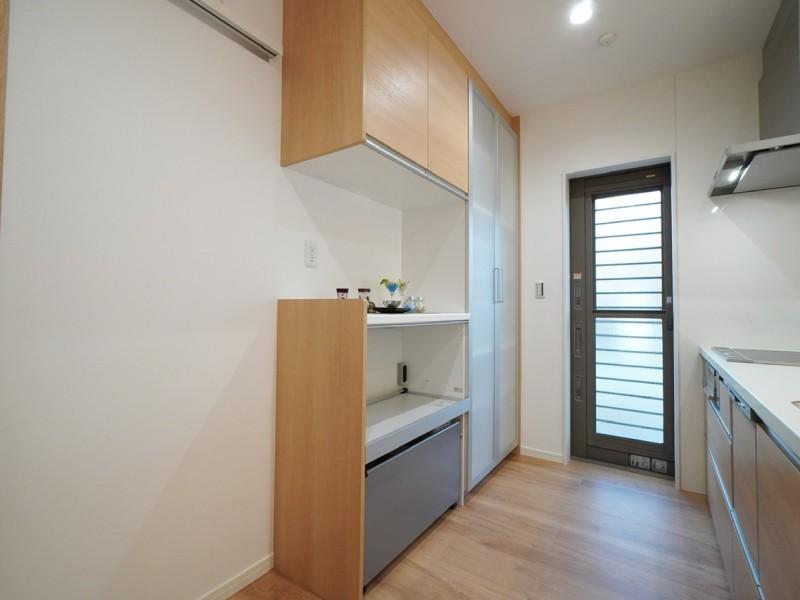 トールタイプと家電収納タイプのキッチン収納も設置済。半透明タイプの扉は最近の流行です。