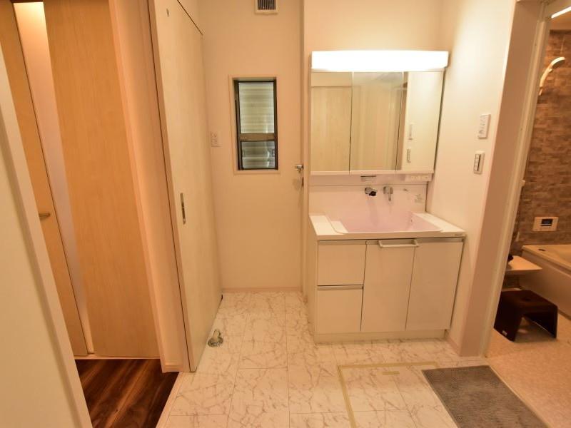 2方向から出入りできる洗面脱衣室です。シャワー付き洗面化粧台が備え付けてあります。