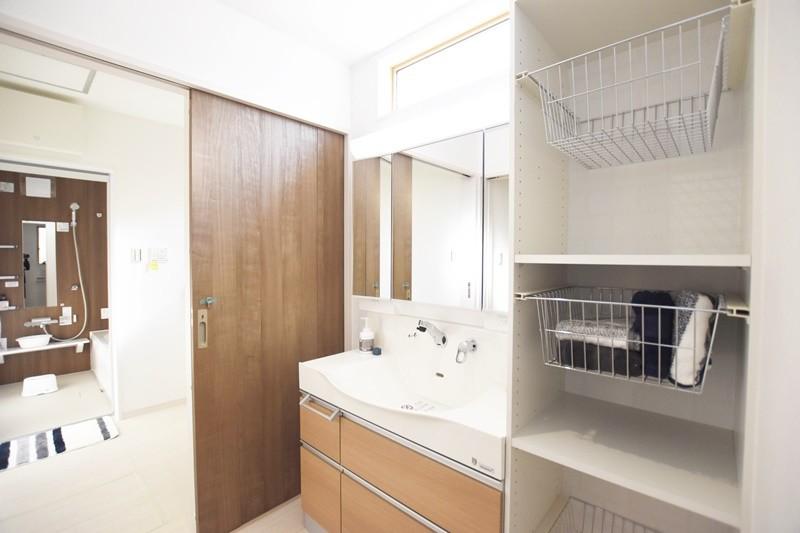 熊本市東区小山5丁目 新築一戸建て 4号地モデルハウス・可動棚付きの洗面室。奥には脱衣室があり、浴室に続きます