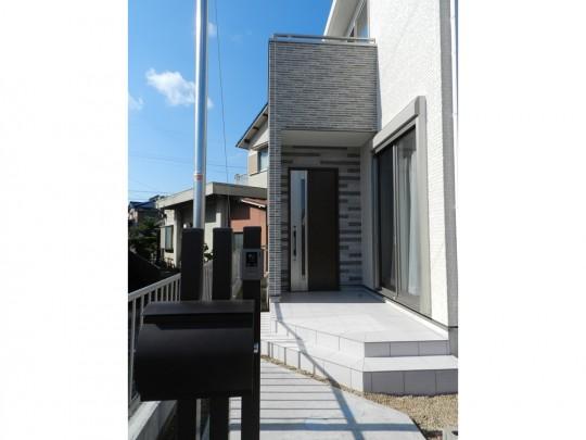 3号地外観:無機質なコンクリートの質感にリアルな木目の風合いをプラスした、印象的な玄関。
