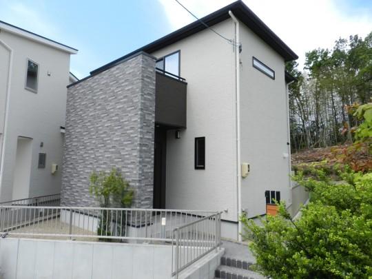 1号地外観:石目調の外壁を使用したバルコニーが、家に重厚感を与えながらも、シンプルなデザイン。