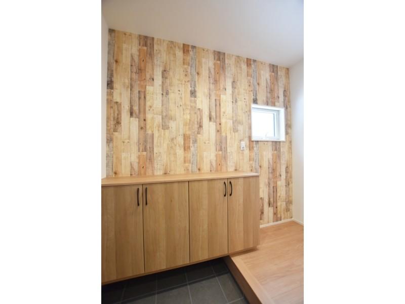 1号地玄関:玄関は印象的な木目の壁紙。家で一番来客が多い場所なので、おしゃれな空間にしました。