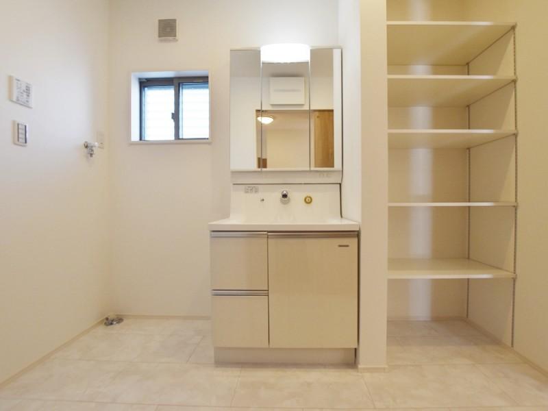 1号地洗面所:シャワー付洗面化粧台が備え付けてあります。また、可動棚にはタオルやランドリー用品等をスッキリ収納出来ます。