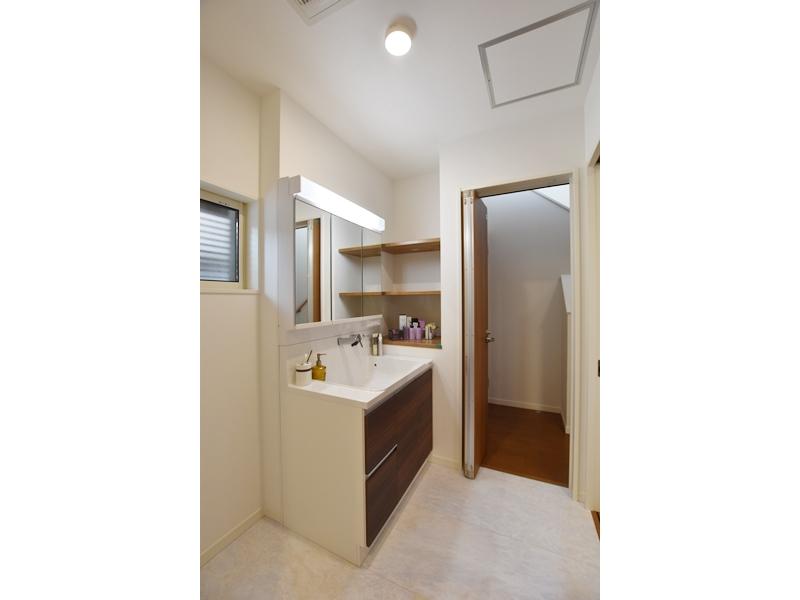 1号地洗面所:洗面台の横に棚を設けました。タオル等はもちろん、ドライヤーを置いたり、シェーバーの充電にも便利です。