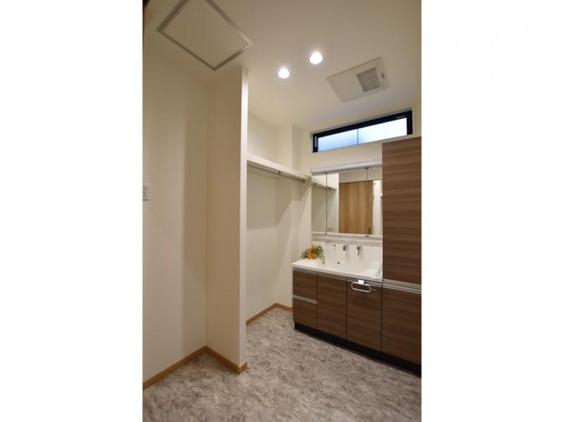 1号地 収納スペースの多い洗面化粧台とハンガーパイプのある脱衣室。