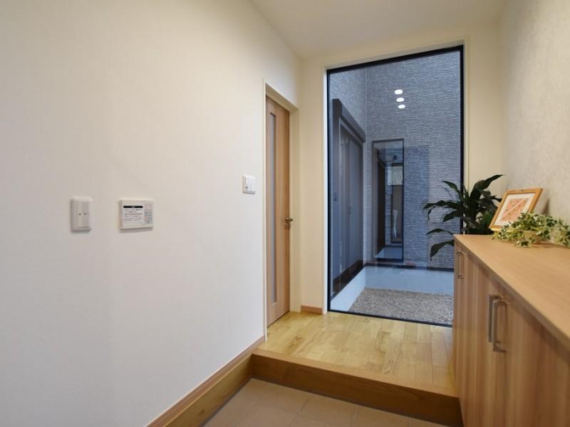 1号地 開放的な窓とリーフのアクセントクロスが特徴的な玄関。